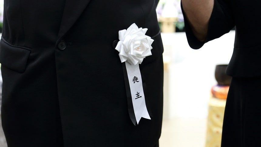 喪主の胸についた喪章