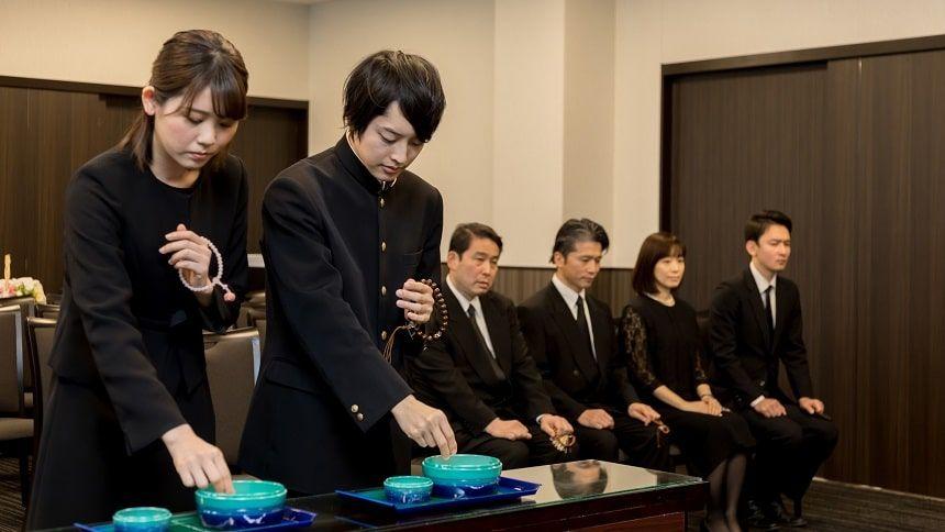 男女の学生が制服を着て焼香をしている姿