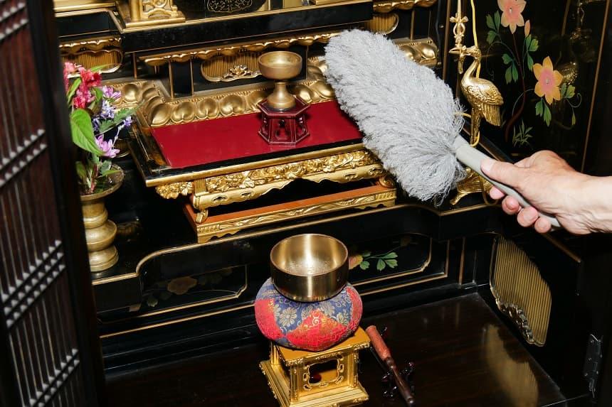 仏壇をモップで掃除している様子