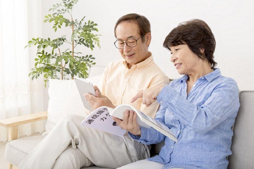 カタログを見て話し合う老夫婦