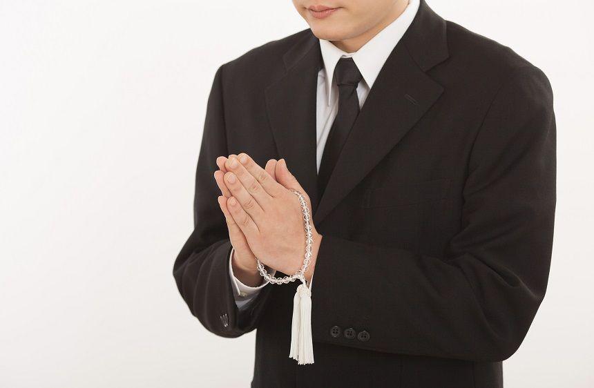 数珠を持って拝んでいる喪服姿の男性