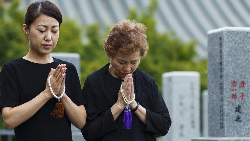 お墓の前で祈る人