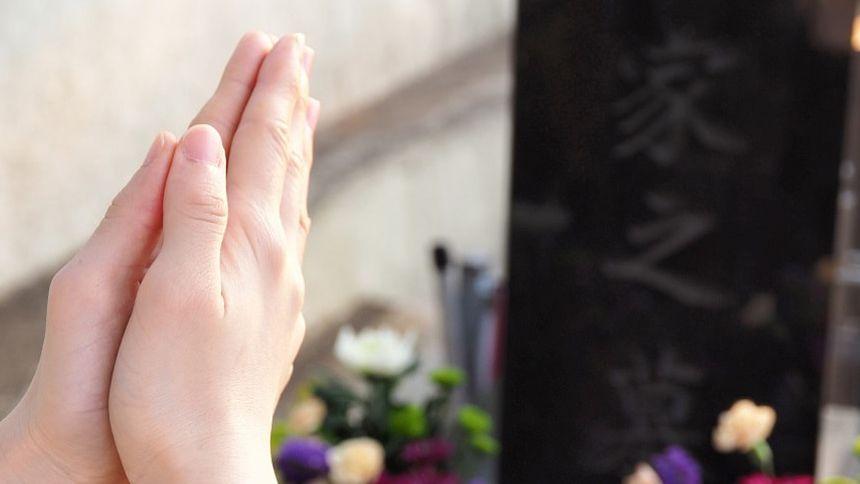 供花が供えられた墓前で合わせている両手