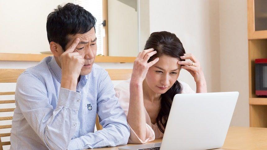 パソコンの前で頭を抱える中年夫婦