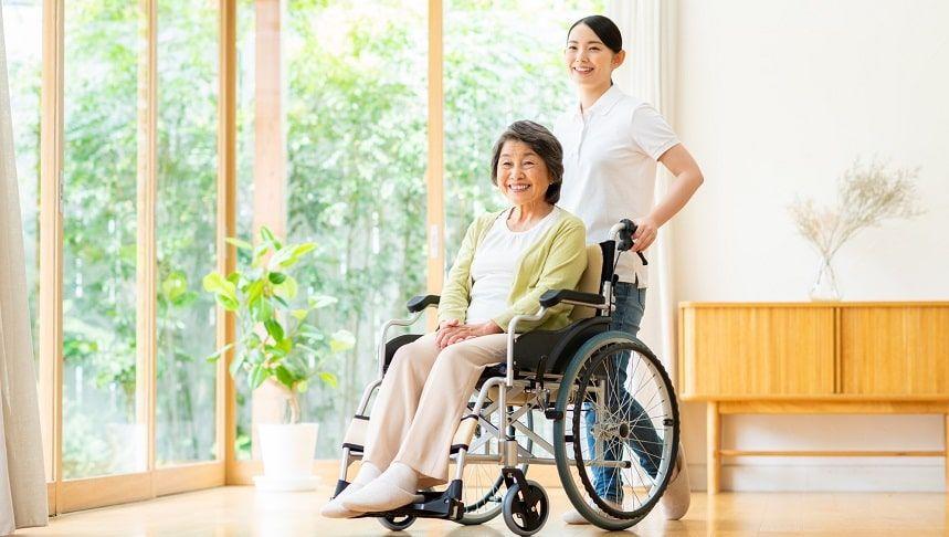 車いすを押す介護士と高齢の女性