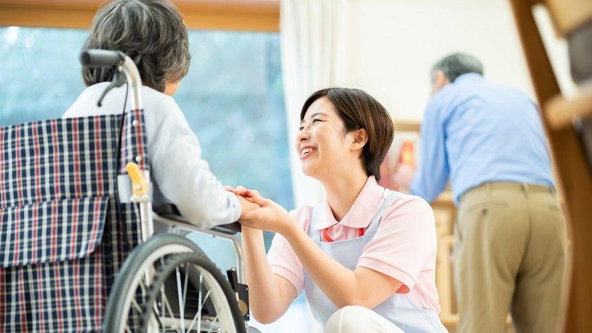 車いすに座っている老婆と向き合う介護士