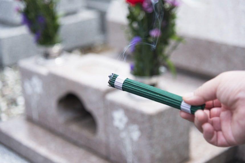 墓前で線香を持つ手