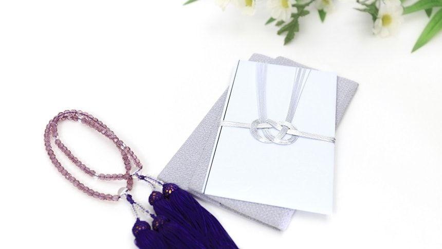 数珠と仏花とグレーの不祝儀袋