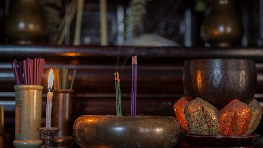 火の灯るろうそくと線香が供えられている仏壇