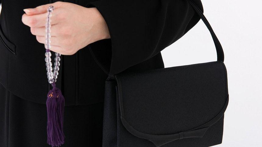 数珠とバッグを持つ喪服姿の女性