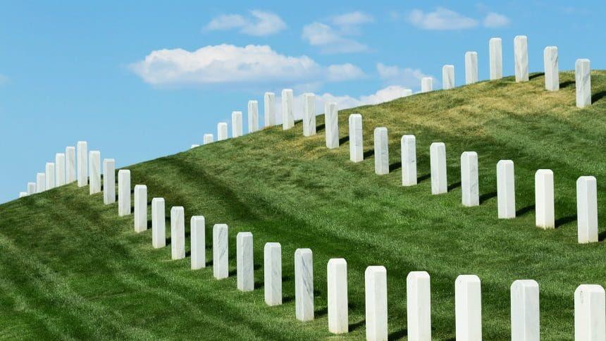 青空の下で丘に並ぶ統一した形の墓石