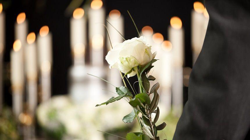ロウソクと白いバラを持つ参列者
