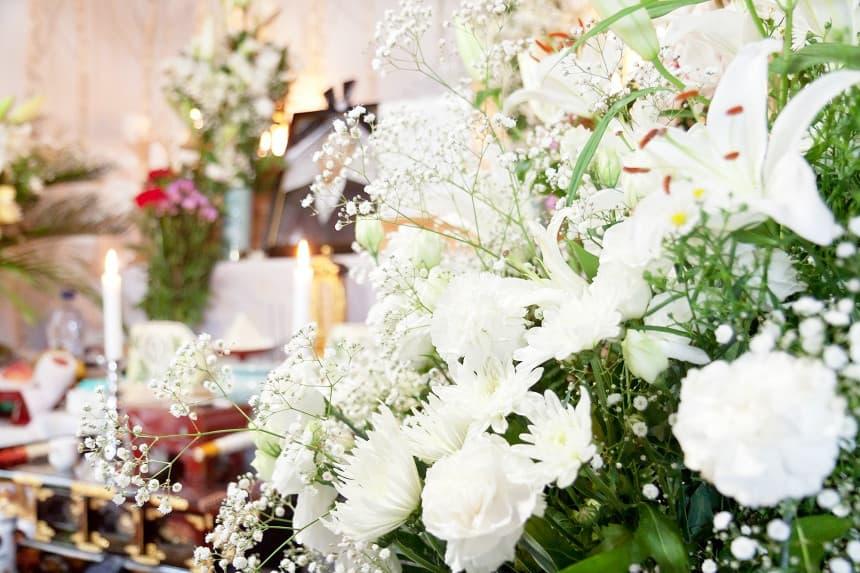 白い供花が飾られている祭壇