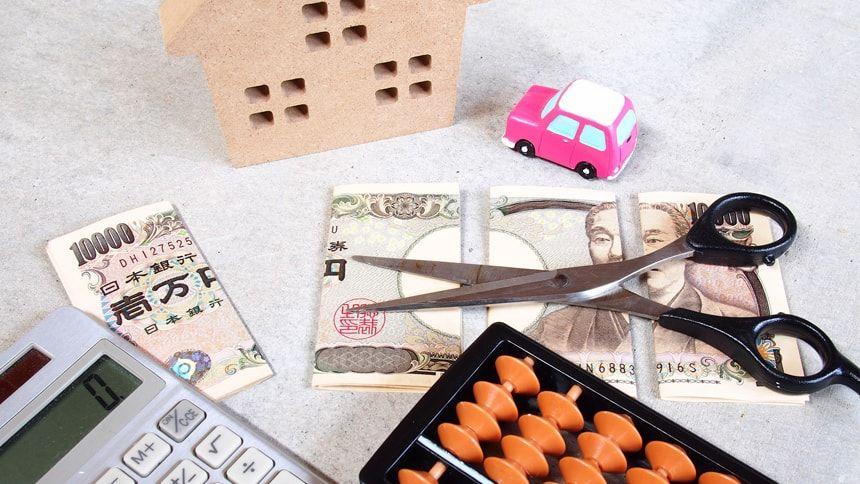 4分割に分かれたお札と電卓と家と車の模型