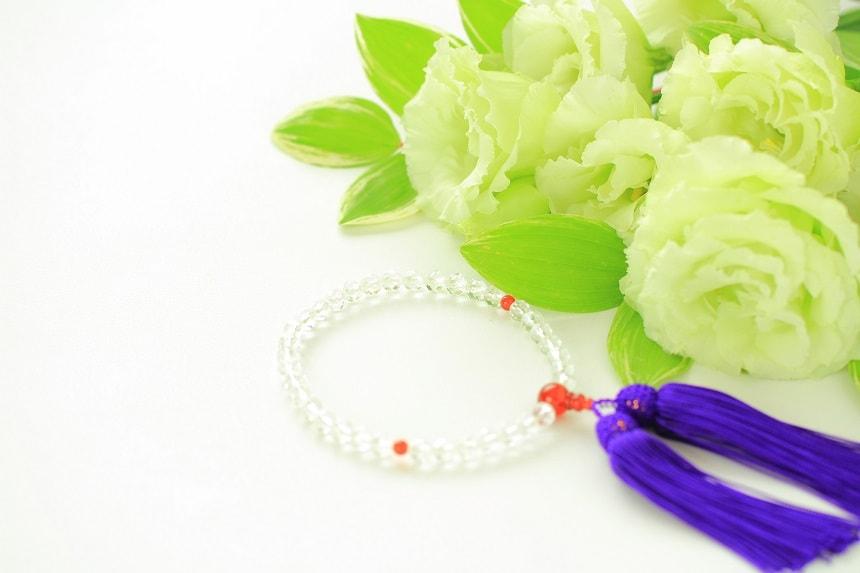 永代供養を表現する数珠と白い菊。