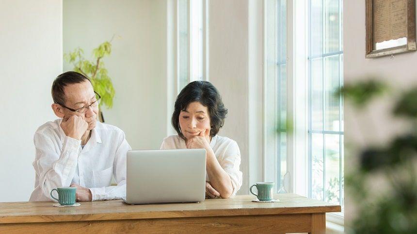 パソコンの前で考える夫婦